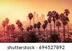 Stock photo beautiful sunset of los angeles downtown skyline and palm trees in foreground 694527892