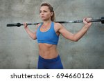 a young girl holds a barbell... | Shutterstock . vector #694660126