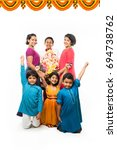 Small photo of Group of Indian Kids holding Ganpati Idol on Ganesh festival or Chaturthi, welcoming god. Standing isolated over white background