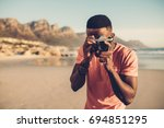 black guy using digital camera... | Shutterstock . vector #694851295