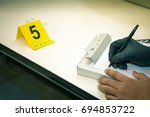 Small photo of forensic hands in glove writing evidence information with evidence marker in cinematic tone and copy space