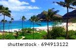 palm trees framing sandy... | Shutterstock . vector #694913122