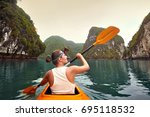 happy woman paddling the kayak... | Shutterstock . vector #695118532