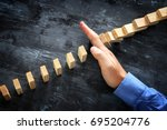 a male hand stopping the domino ... | Shutterstock . vector #695204776
