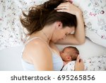 young mother breastfeeds her... | Shutterstock . vector #695265856