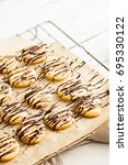 Small photo of Baked butter cookies with dark chocolate drizzle glaze on a baking paper and wire rack. White wooden table.