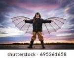 boy with wings at sunset... | Shutterstock . vector #695361658