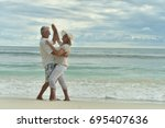 Small photo of Happy elderly couple dancing on tropical beach