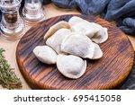 frozen dumplings on a wooden... | Shutterstock . vector #695415058