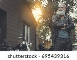 Small photo of Crackerjack old male person having rest near bike