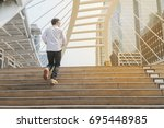 young man walking up stair in... | Shutterstock . vector #695448985
