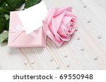 Small pink Valentine's day gift with tie, pearls and copy space card. - stock photo