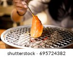 people grilling meat on fire ... | Shutterstock . vector #695724382