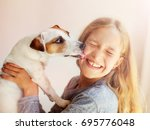 Stock photo happy child with dog portrait girl with pet jack russell licks a teen 695776048