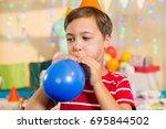 cute boy blowing balloon during ... | Shutterstock . vector #695844502