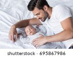 handsome father lying on bed... | Shutterstock . vector #695867986