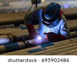 male in face mask welds with... | Shutterstock . vector #695902486
