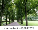 big trees in alley with foot... | Shutterstock . vector #696017692