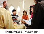 Islamic education inside white mosque, teacher and children learning together (or mother and father with them) - stock photo