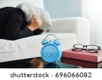 Small photo of Sleepy Asian Business woman in black shirt covering ears with pillow on sofa and Alarm clock, Glasses, Notebook on side table. Female having trouble waking up. Stress from overtime working concept.