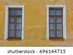 two old windows on the yellow... | Shutterstock . vector #696144715