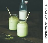 Small photo of Cold refreshing iced coconut matcha latte drink in glass jars. Selective focus, copy space, dark background, square crop. Clean eating, healthy, vegetarian, alkaline diet, dairy free food concept