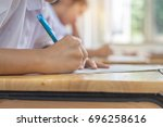 Small photo of Students using pen writing information on white answer paper in high school, Asian exams room, Tests or examination is assessment intended to measure knowledge, skill, aptitude, Education Concept