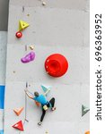 Small photo of Sportsman or amateur starts to climbing big artificial wall at modern colorful indoor boulder gym