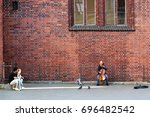 Small photo of RIGA, LATVIA - JULY 10, 2017: Man plays cello near the Riga Dome Cathedral of Saint Mary in old town of Riga, famous for its pipe organ and acoustics.