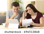 worried couple reading together ... | Shutterstock . vector #696513868