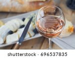 Stock photo a glass of rose wine served with cheese plate blackberries and baguette assortment of cheese with 696537835
