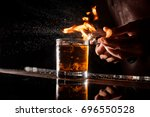 Stock photo the bartender makes flame over a cocktail with orange peel close up 696550528
