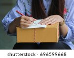 woman signing receipt of... | Shutterstock . vector #696599668