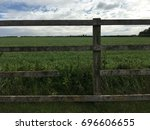 Small photo of Fence with a missing link in front of a green field and sky with white clouds in Somerset in England