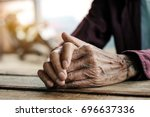 hands of an old man on the wood ... | Shutterstock . vector #696637336