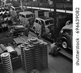 Small photo of Factory workers putting hub cabs on cars on assembly line