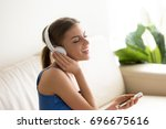 Small photo of Portrait of pretty young woman in headphones sitting on sofa, listening music with mobile phone and signing. Beautiful millennial lady enjoying her favorite musical composition while resting at home