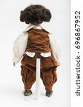Small photo of Ceramic porcelain handmade vintage doll of brunette boy with curly hair in in old brown crumpled velour masquerade costume with vest and elegant shirt with embroidery on white background.