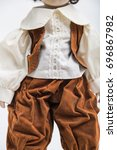 Small photo of Portrait of ceramic porcelain handmade vintage doll of brunette boy with curly hair in in old brown crumpled velour masquerade costume with vest and elegant shirt with embroidery on white background.