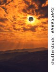 Small photo of Amazing scientific natural phenomenon. The Moon covering the Sun. Total solar eclipse with diamond ring effect glowing on sky above mountain range. Serenity nature background.