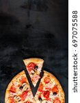 pizza with a slice on a dark... | Shutterstock . vector #697075588