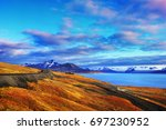 Small photo of Beautiful scenic view - tundra land covered with bright yellow and orange moss, desert road and blue gulf under barren mountains near Barentsburg, Svalbard (Spitsbergen island), Norway, Greenland sea
