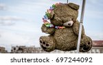 Hanging teddy bear with a colorful necklace - stock photo