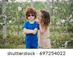 little boy and girl in blooming ... | Shutterstock . vector #697254022