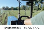 farmer driving tractor on the... | Shutterstock . vector #697374772