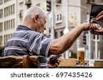 BRATISLAVA, SLOVAKIA - August 12, 2017: An old man in retirement age paying for his beer - stock photo