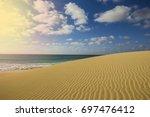 a natural sand dune along the... | Shutterstock . vector #697476412