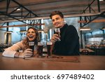 Small photo of Smiling young couple at the bar with different varieties of craft beers. They are at brewery and tasting beers.