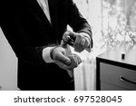 the groom is holding perfume.... | Shutterstock . vector #697528045