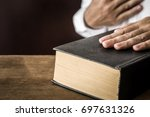 Small photo of Man's hand swearing on the bible. Taking an oath.